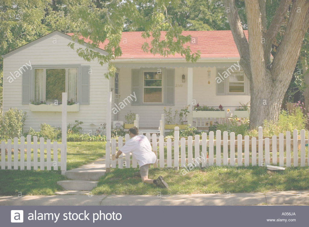 Fabulous Man Painting White Picket Fence In Front Of House Stock Photo for Painting House White