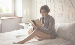 Cool Woman Reading Book While Sitting On Bed In Bedroom At Home - Stock in Good quality Sitting On Bed